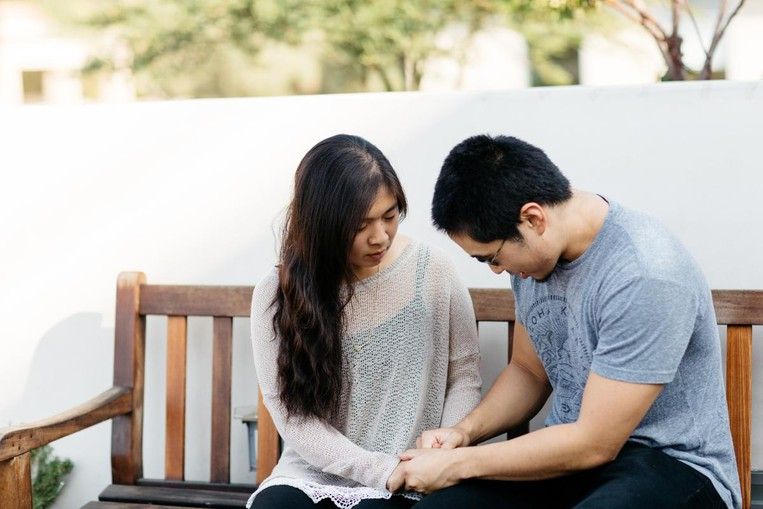 young couple holding hands in prayer