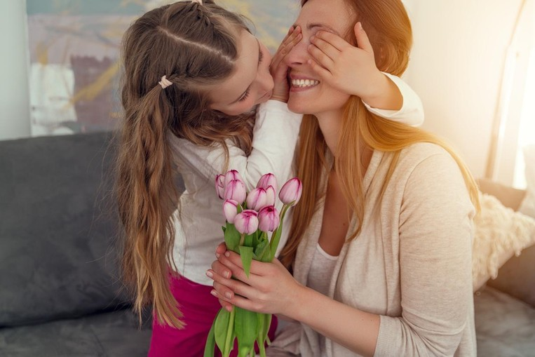 Little girl covering her mother's eyes while presenting her with a bouquet of flowers