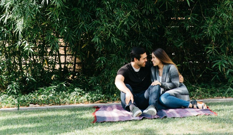 Couple sitting close together outside on a blanket, smiling.