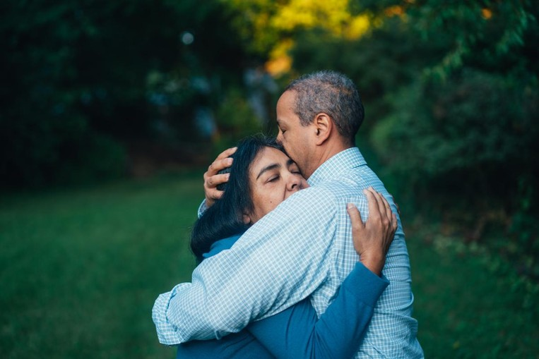 African American man and woman embrace with eyes closed.